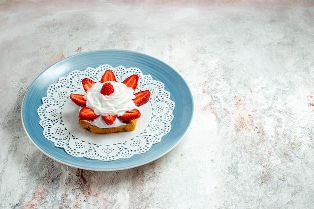 Widok z przodu pyszne małe ciasto ze śmietaną i truskawkami na białym biurku