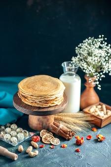 Widok z przodu pyszne naleśniki z mlekiem na ciemnym śniadaniu ciasto miodowe ciasto rano herbata deserowe mleko słodkie