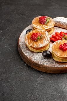 Widok z przodu pyszne naleśniki z owocami i ciastami na ciemnej powierzchni słodkie ciasto owocowe