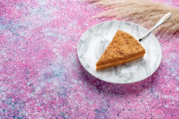 Widok z przodu pyszne okrągłe ciasto kawałek wewnątrz płyty na jasnoróżowym biurku ciasto biszkoptowe słodkie wypieki