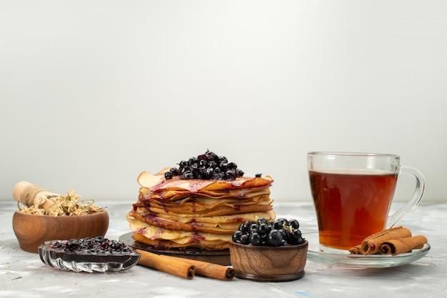 Widok z przodu pyszne okrągłe naleśniki pyszne i okrągłe uformowane z jagodami i cynamonowym ciastem naleśnikowym