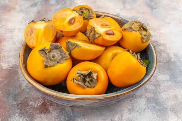 Widok z przodu pyszne persimmons w misce na nagim tle