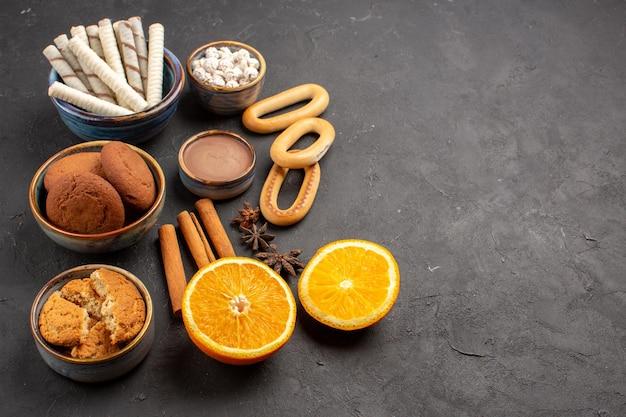 Widok z przodu pyszne piaskowe ciasteczka ze świeżymi pokrojonymi pomarańczami na ciemnym tle ciastko słodkie cytrusowe ciastka z cukrem