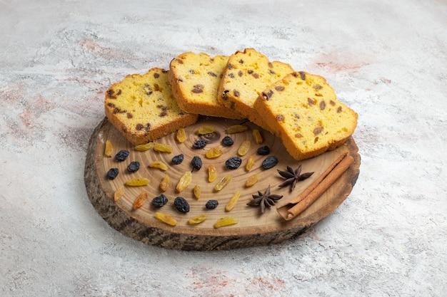 Widok z przodu pyszne plastry ciasta z rodzynkami na jasnobiałej powierzchni