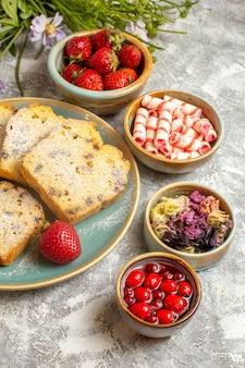 Widok z przodu pyszne plastry ciasta z truskawkami na jasnej powierzchni słodkie ciasto owocowe