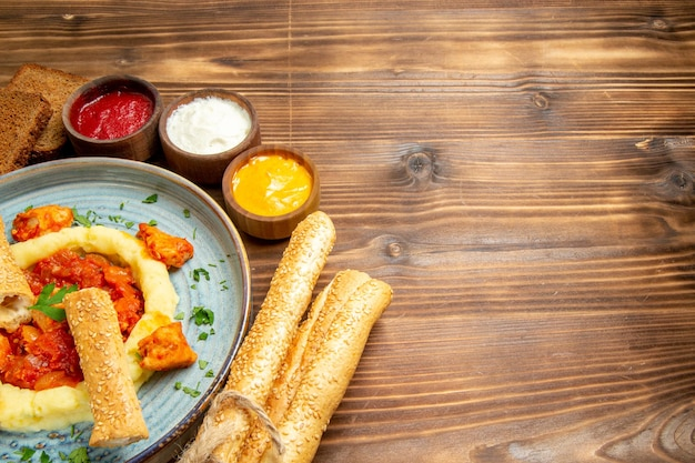 Widok z przodu pyszne plastry kurczaka z puree ziemniaczanym i chlebem na drewnianym biurku ziemniaki posiłek jedzenie pikantna papryka