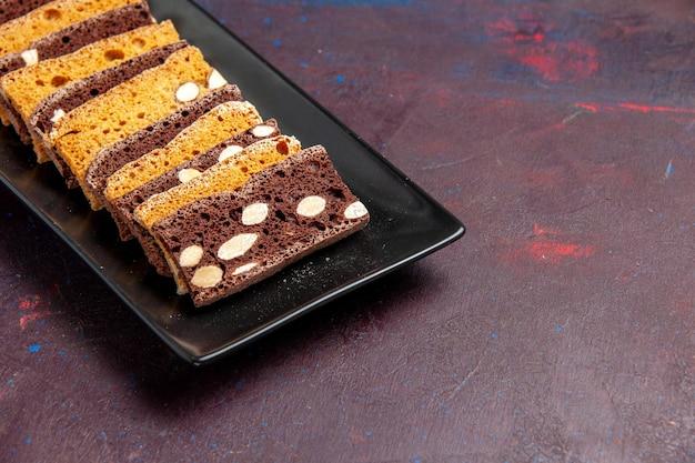 Widok z przodu pyszne pokrojone ciasto z orzechami wewnątrz formy do ciasta na ciemnej przestrzeni