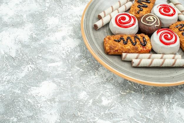Widok z przodu pyszne słodkie ciasteczka i ciasta na białej przestrzeni
