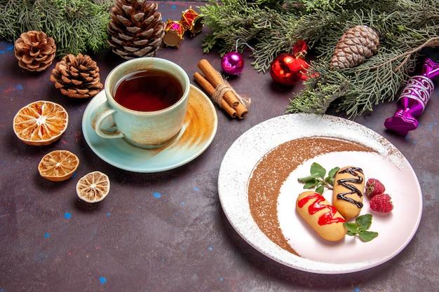 Widok z przodu pyszne słodkie ciasteczka z filiżanką herbaty na ciemnej przestrzeni