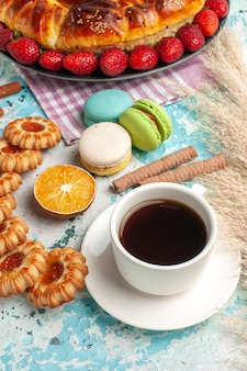 Widok z przodu pyszne słodkie ciasto z czerwonymi truskawkowymi ciasteczkami i herbatą na niebieskiej powierzchni