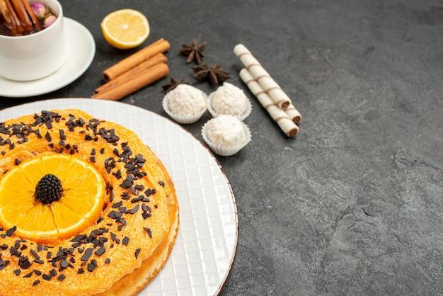 Widok z przodu pyszne słodkie ciasto z filiżanką herbaty na szarym tle deser słodkie ciasto ciasto herbatniki herbata