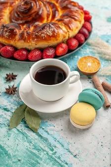 Widok z przodu pyszne słodkie ciasto z macarons truskawkami i filiżanką herbaty na niebieskiej podłodze