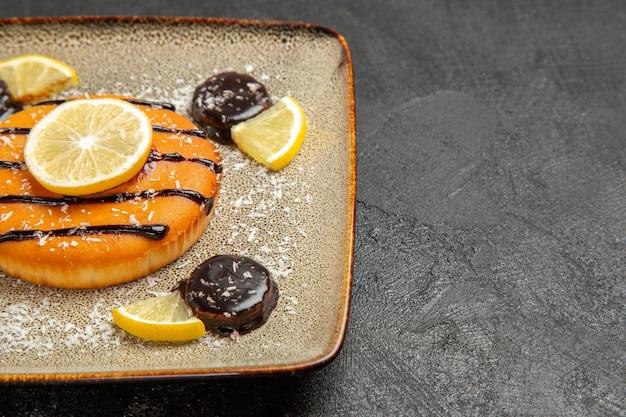 Widok z przodu pyszne słodkie ciasto z sosem czekoladowym i plasterkami cytryny na szarym tle ciasto ciastko ciasto biszkoptowe słodkie ciasteczka