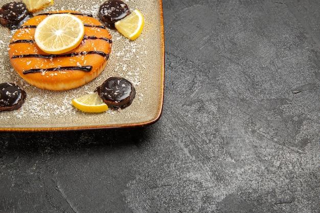Widok z przodu pyszne słodkie ciasto z sosem czekoladowym i plasterkami cytryny na szarym tle