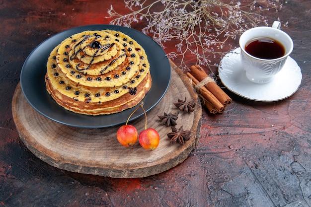 Widok z przodu pyszne słodkie naleśniki z filiżanką herbaty na ciemnym tle