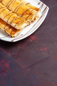Widok z przodu pyszne słodkie wypieki wewnątrz talerza na ciemnofioletowym biurku