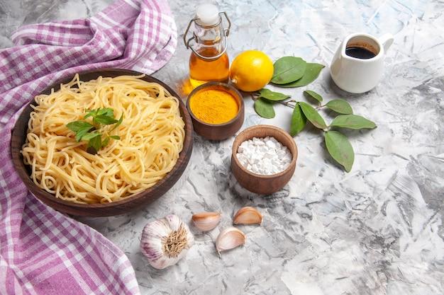 Widok z przodu pyszne spaghetti wewnątrz talerza na białym stole naczynie z ciasta makaronowego