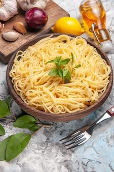Widok z przodu pyszne spaghetti z czosnkiem na białym stole makaron ciasto mąka papryka