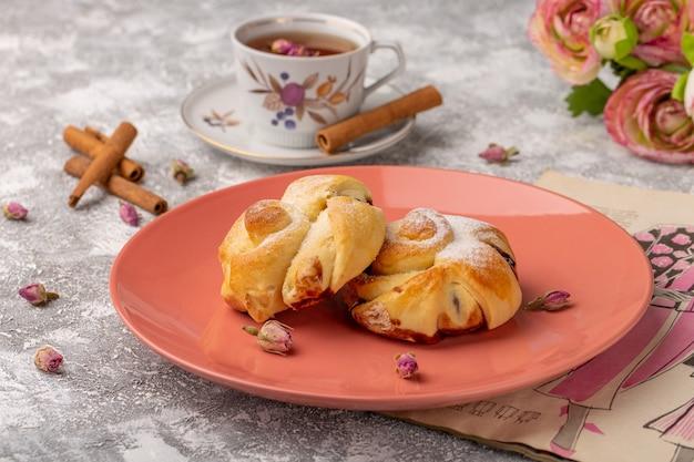 Widok z przodu pyszne wypieki z nadzieniem wewnątrz talerza wraz z herbatą i cynamonem na białym stole, słodkie ciasto cukrowe piec ciasto