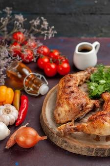 Widok z przodu pysznego smażonego kurczaka ze świeżymi warzywami i zieleniną na ciemnym miejscu