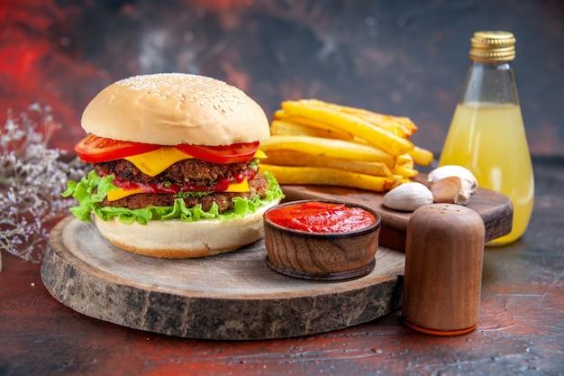 Widok z przodu pyszny burger mięsny z frytkami na ciemnym tle