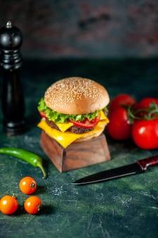 Widok z przodu pyszny cheeseburger na ciemnym tle