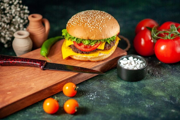 Widok z przodu pyszny cheeseburger z pomidorami na ciemnym tle
