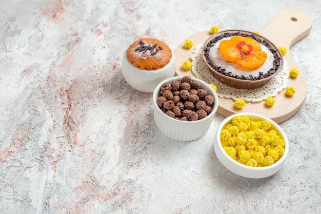 Widok z przodu pyszny deser czekoladowy z mandarynkami i cukierkami na białej przestrzeni
