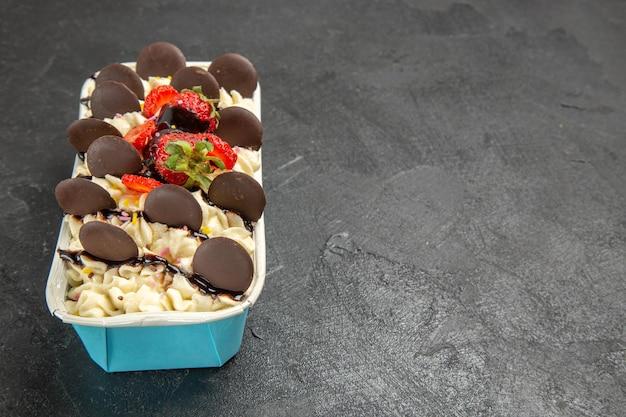 Widok z przodu pyszny deser z czekoladowymi ciasteczkami i truskawkami na ciemnym tle orzechowe słodkie owocowe ciastko z jagodami