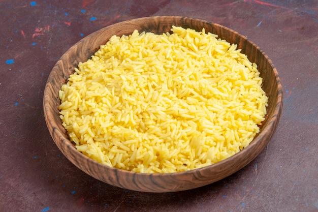 Widok z przodu pyszny gotowany ryż wewnątrz brązowego talerza w ciemnej przestrzeni