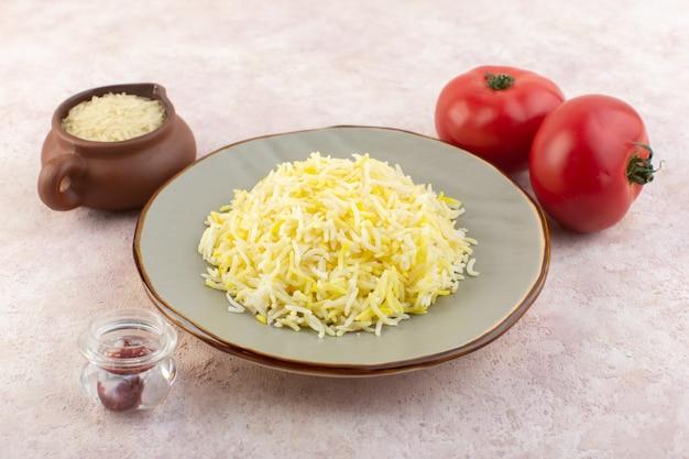 Widok z przodu pyszny gotowany ryż wewnątrz płyty wraz ze świeżymi czerwonymi pomidorami na różowym stole jedzenie posiłek ryż warzywny