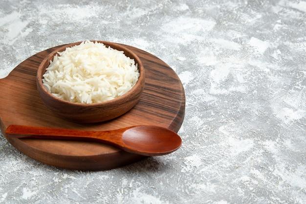 Widok z przodu pyszny gotowany ryż wewnątrz talerza na białej przestrzeni