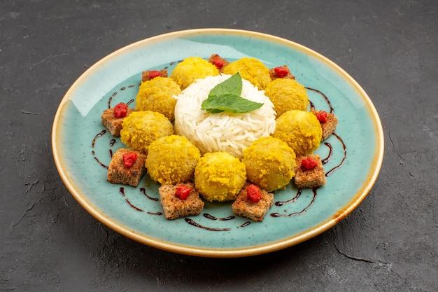 Widok z przodu pyszny gotowany ryż z klopsikami wewnątrz talerza na ciemnej przestrzeni