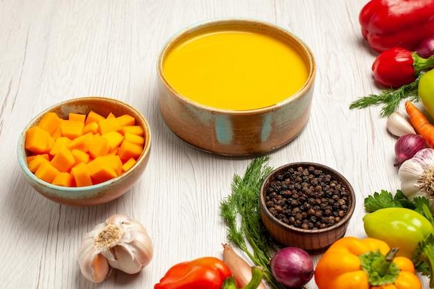 Widok z przodu pyszny krem z zupy dyniowej z teksturą z warzywami na białym biurku z dojrzałym sosem do zupy