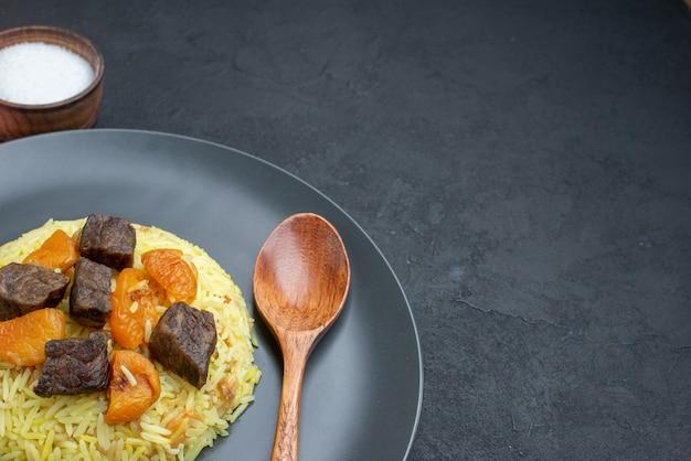 Widok z przodu pyszny pilaw gotowany ryż z solą plastry mięsa na ciemnej powierzchni