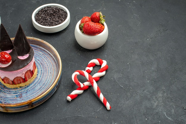 Widok z przodu pyszny sernik z truskawkami i czekoladą na miskach talerzowych z truskawkami czekoladowe cukierki świąteczne na ciemnym na białym tle z miejscem na kopię