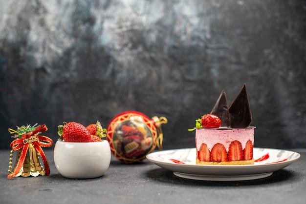 Widok z przodu pyszny sernik z truskawkami i czekoladą na owalnym talerzu miska truskawek zabawki świąteczne