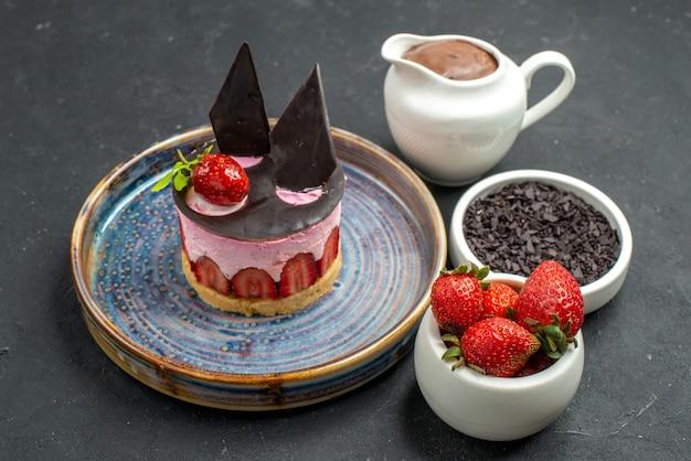 Widok z przodu pyszny sernik z truskawkami i czekoladą na talerzu miseczki z czekoladowymi truskawkami