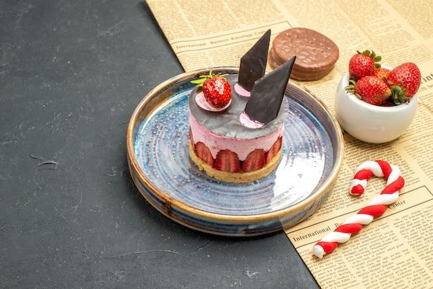Widok z przodu pyszny sernik z truskawkami i czekoladą na talerzu miska truskawkowa herbatniki świąteczne cukierki