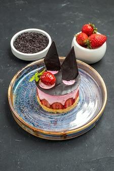 Widok z przodu pyszny sernik z truskawkami i czekoladą na talerzu miski z truskawkami czekolada na ciemnym