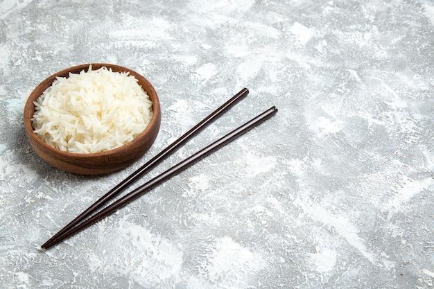 Widok z przodu pyszny ugotowany ryż wewnątrz brązowego talerza na białej przestrzeni