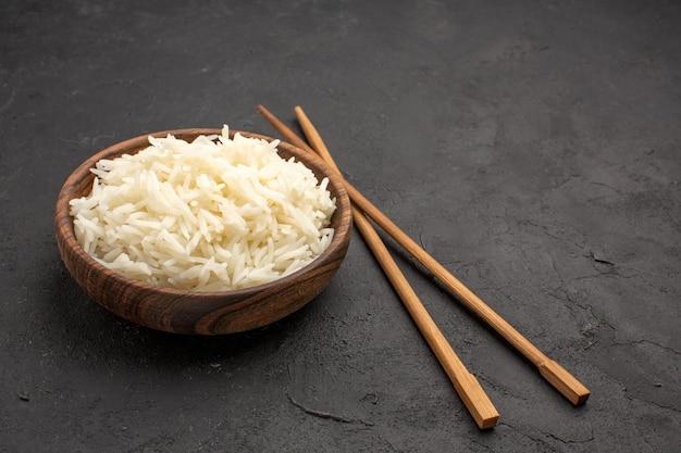 Widok z przodu pyszny ugotowany ryż zwykły smaczny posiłek wewnątrz talerza na ciemnym biurku