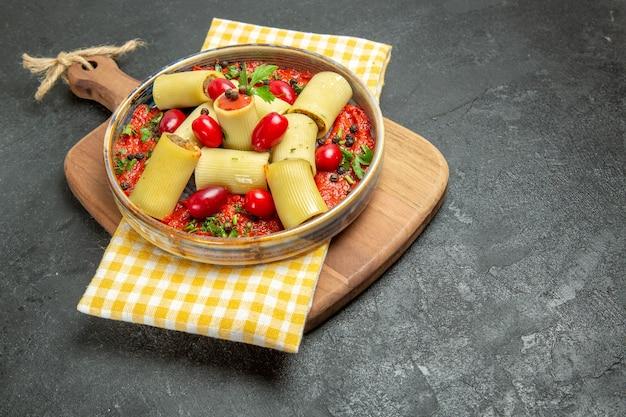 Widok z przodu pyszny włoski makaron z mięsem i sosem pomidorowym na szarym tle posiłek makaron ciasto jedzenie obiad