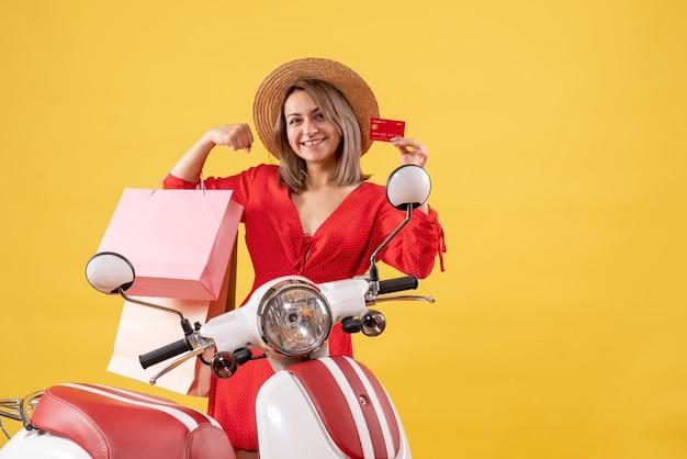 Widok z przodu radosnej kobiety w czerwonej sukience na motorowerze, trzymając torby na zakupy i karty