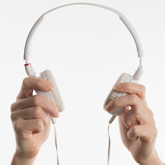 Widok z przodu rąk trzymających słuchawki