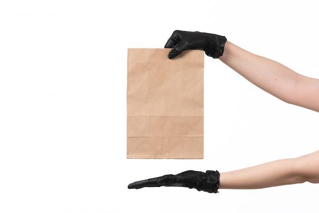 Widok z przodu ręce kobiet na sobie czarne rękawiczki, trzymając pakiet papieru na białym tle