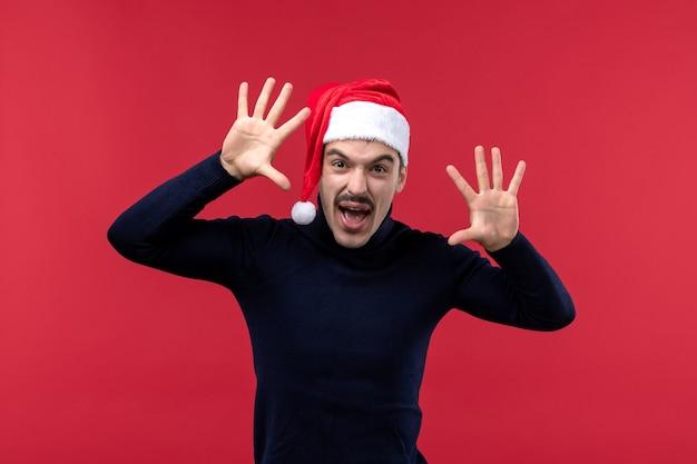 Widok z przodu regularnego mężczyzny z przerażającym wyrazem na czerwonym tle