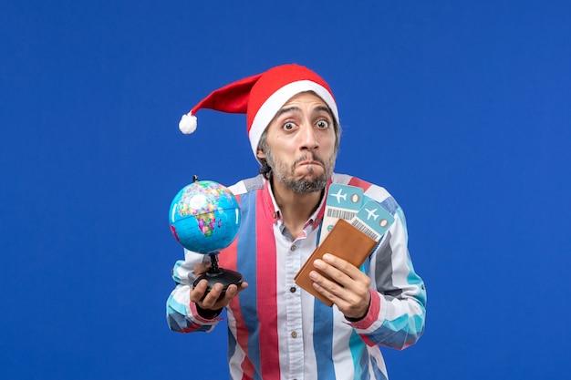 Widok z przodu regularny mężczyzna z biletami i kulą ziemską na niebieskich kolorach ścian wakacje nowy rok