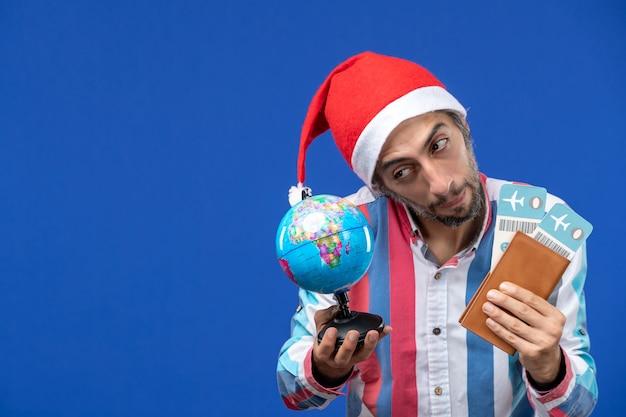 Widok z przodu regularny mężczyzna z biletami i kulą ziemską na niebieskiej ścianie emocje wakacje nowy rok