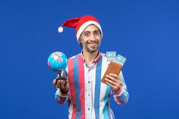 Widok z przodu regularny mężczyzna z biletami i kulą ziemską na niebieskiej ścianie kolor wakacje nowy rok